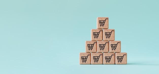Écran d'impression de panier de caddie sur bloc de cube en bois empilé sur fond bleu pour signe d'augmentation du volume de vente et concept de croissance des commandes par rendu 3d.