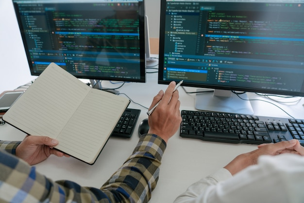 L'écran de jeunes programmeurs assis à un bureau travaillant sur des ordinateurs pour développer la programmation et le codage pour trouver une solution au problème sur une nouvelle application