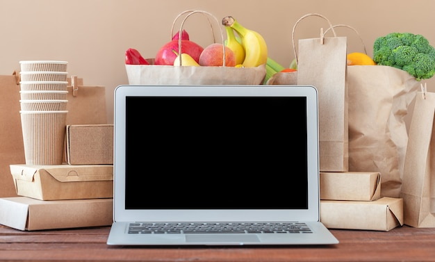 Écran d'ordinateur de concept de livraison de nourriture et paquets de nourriture