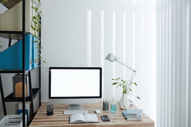Écran d'ordinateur avec écran vide, livres, planificateur et désinfectant pour les mains sur la table dans le bureau à domicile de la personne