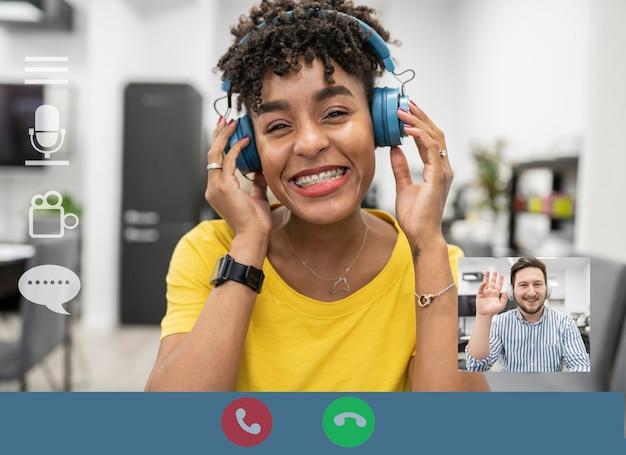 Écran d'ordinateur avec une jeune femme afro-africaine en réponse à un appel vidéo et un homme sur un écran miniature