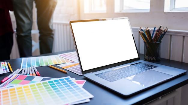 Écran d'ordinateur portable blanc vierge de graphistes mis sur la table de bureau en co-working