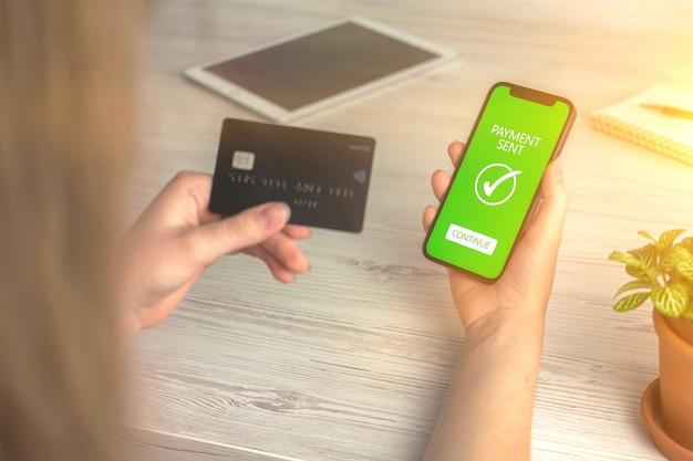 Écran de paiement envoyé et carte de crédit dans la main de la femme, banque en ligne et photo d'arrière-plan de transfert d'argent