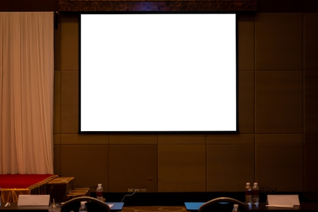 Écran de projection vierge dans une salle de séminaire ou une salle de conférence. chemin de détourage inclus dans l'affichage.