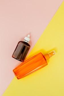 Écran solaire de bouteille sur carré jaune et rose vif
