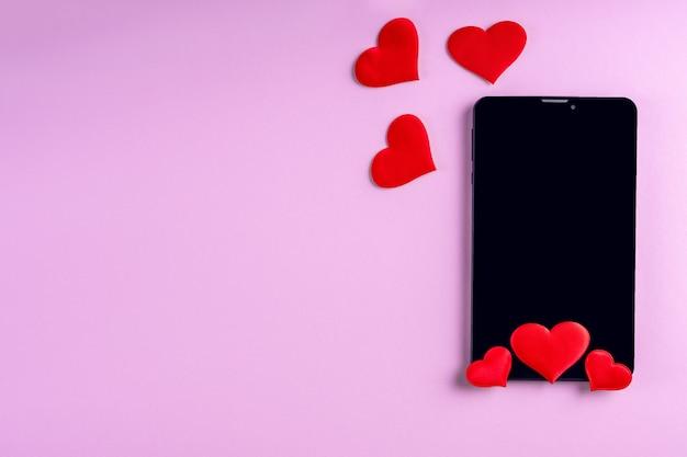 Écran de téléphone blanc noir avec forme de coeur rouge sur fond rose, espace copie