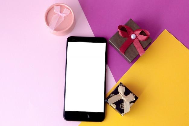 Écran de téléphone et cadeaux sur fond coloré. concept minimal. mise à plat. vue de dessus promotions et remises en ligne. cadeaux de vacances et surprises. présent. la saint-valentin. technologies internet