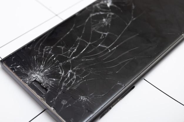 L'écran de verre brisé du smartphone repose sur la tablette pour réparation