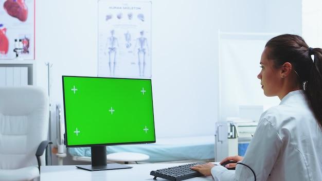 Écran vert de clé chroma sur l'ordinateur dans l'armoire de l'hôpital pendant que le médecin y travaille. infirmière en uniforme bleu en arrière-plan. ordinateur avec écran remplaçable utilisé par un spécialiste de la médecine à l'hôpital