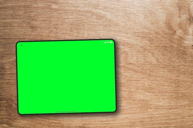 Écran vert de la tablette sur fond en bois. vue de dessus. clé chroma.