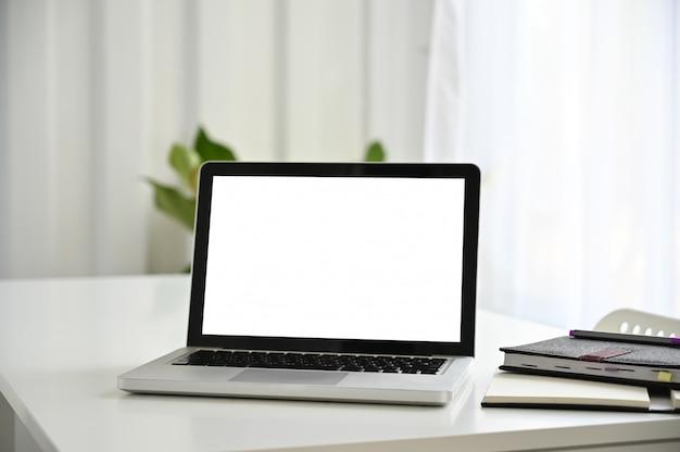 Écran vide d'ordinateur portable sur un tableau blanc avec du papier de cahier.