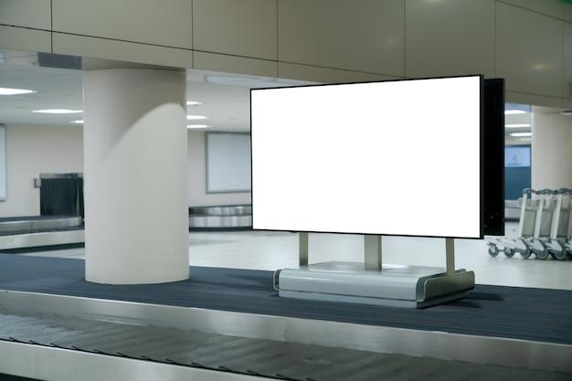 Écran vierge de maquette à bagages à bande transporteuse à l'aéroport. écran blanc pour la publicité textuelle.
