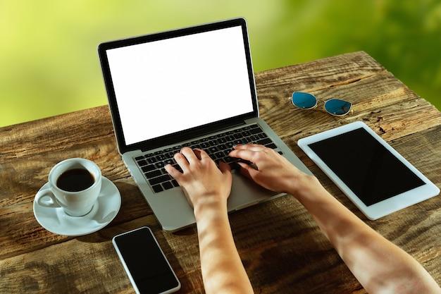 Écrans vierges d'ordinateur portable et de smartphone sur une table en bois à l'extérieur avec la nature sur le mur café à proximité. concept de lieu de travail créatif, entreprise, indépendant. copyspace. mains tapant du texte.