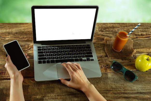 Écrans vierges d'ordinateur portable et de smartphone sur une table en bois à l'extérieur avec la nature sur le mur fruits et jus de fruits frais à proximité. concept de lieu de travail créatif, entreprise, indépendant. copyspace.