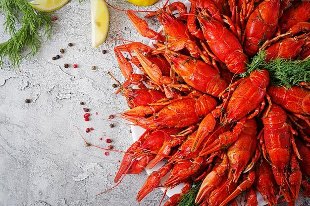Écrevisse. poissons craw bouillis rouges sur table dans un style rustique, gros plan. gros plan de homard. conception de bordure