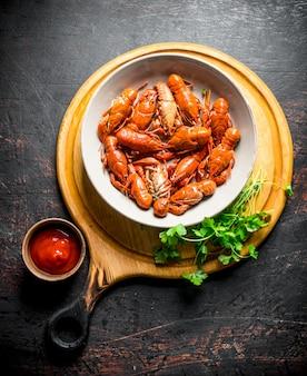 Écrevisses bouillies dans un bol sur une planche à découper avec du persil et de la sauce sur table rustique sombre