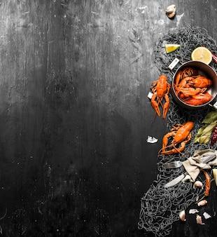 Écrevisses bouillies pour filet de pêche aux épices et herbes. sur un tableau noir.
