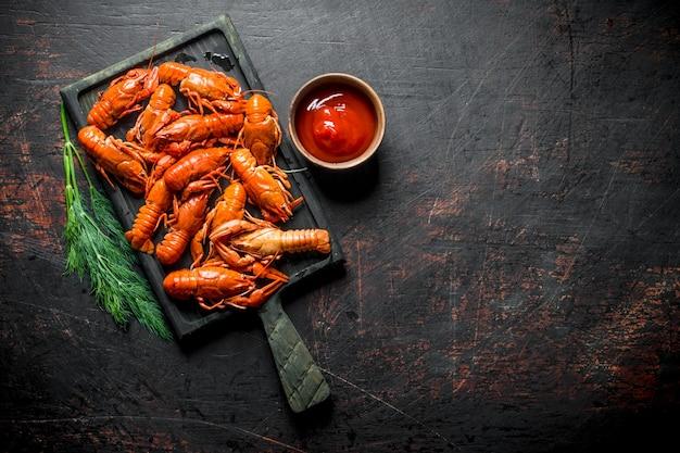 Écrevisses cuites sur une planche à découper avec de l'aneth et de la sauce tomate.