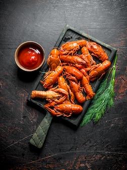 Écrevisses rouges bouillies sur une planche à découper avec sauce et aneth.