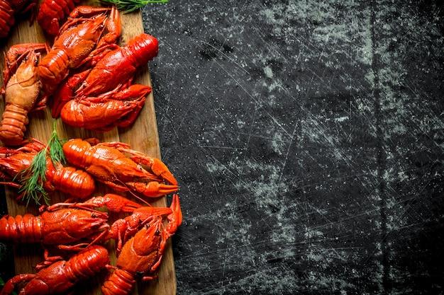 Écrevisses rouges fraîchement cuites sur une planche à découper. sur fond rustique foncé
