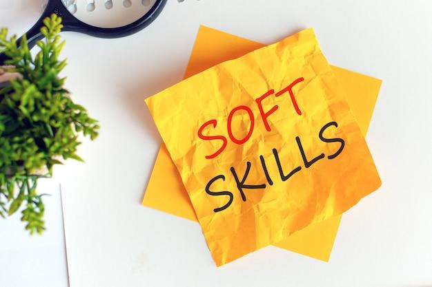 Écrire des compétences non techniques sur du papier jaune froissé, lieu de travail, remue-méninges. défocaliser. lettres rouges.