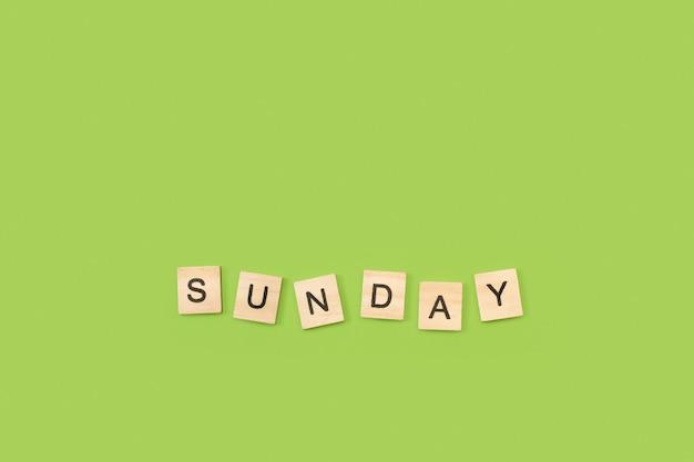 Écrire le dimanche avec des cubes de lettres en bois sur fond vert