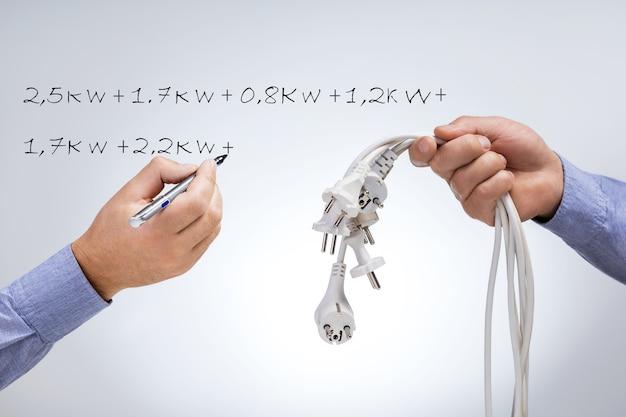 Écrire à la main les valeurs de puissance électrique sur un tableau gris pendant l'audit énergétique. économisez le concept d'électricité.