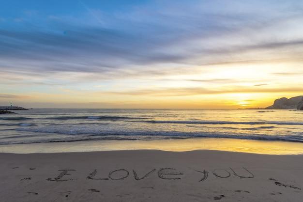 Écrit je t'aime dans le sable sur la plage