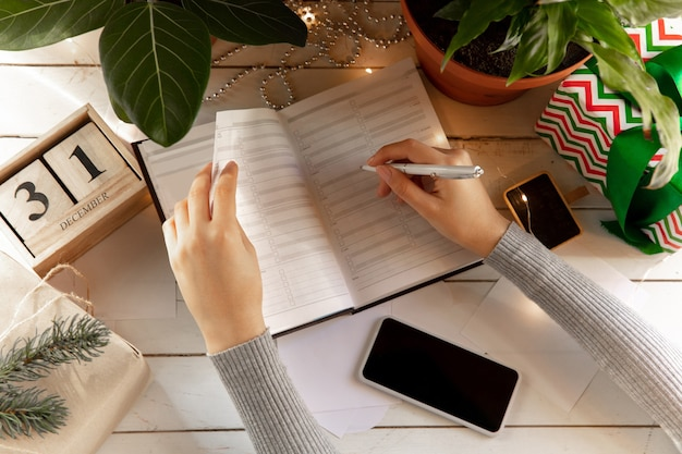 Écrit des souhaits, des rêves et des objectifs en faisant un plan pour le nouvel an et noël