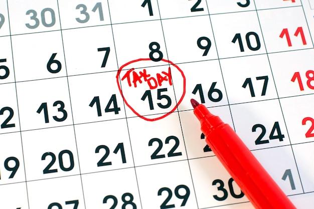 Écriture du jour de l'impôt sur le calendrier mensuel du 15 avril encerclé dans le cercle dans un marqueur rouge.