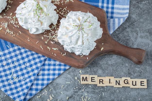 Écriture de meringue avec des dés de lettre autour des cookies.