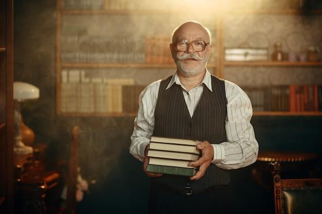 L'écrivain âgé détient une pile de livres au bureau à domicile
