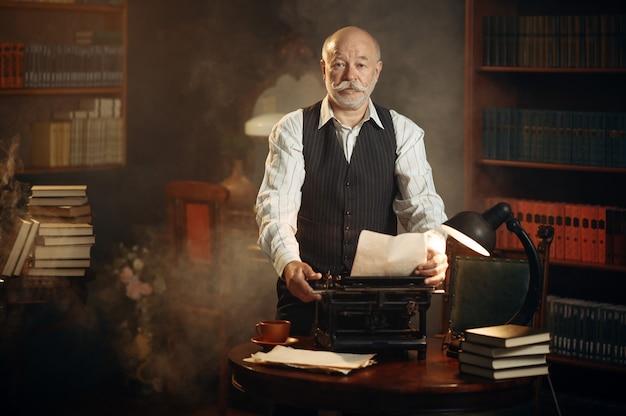 L'écrivain âgé souriant travaille sur une machine à écrire rétro