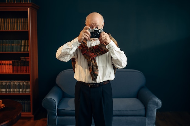 L'écrivain âgé tient un appareil photo rétro au bureau à domicile. vieil homme à lunettes écrit un roman littéraire dans la chambre avec de la fumée