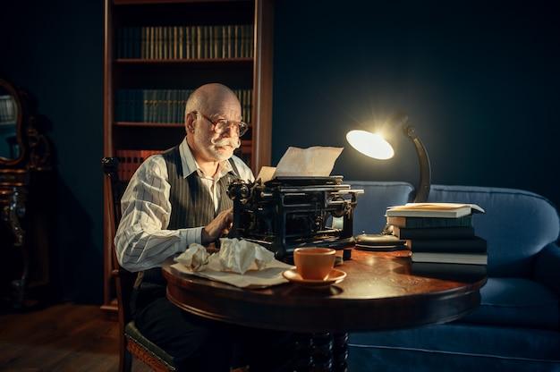 L'écrivain âgé travaille sur une machine à écrire vintage