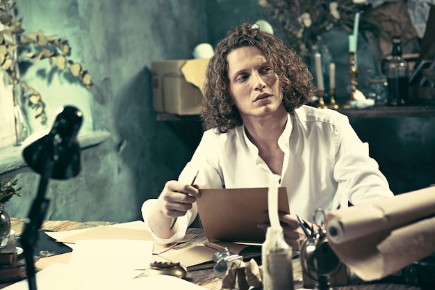 Écrivain au travail. beau jeune écrivain assis à la table et écrit quelque chose dans son carnet de croquis à la maison