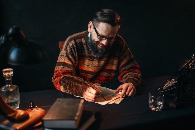 Écrivain barbu dans des verres écrit avec une plume
