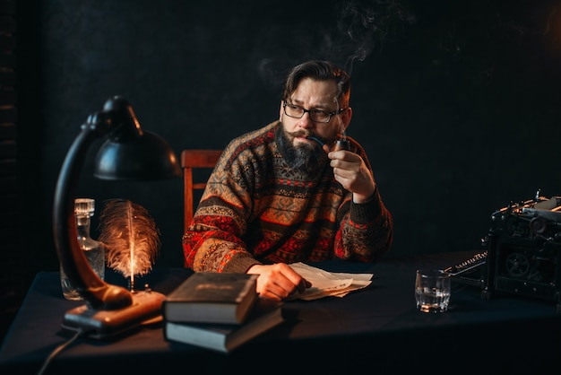 Écrivain barbu dans des verres fumant une pipe