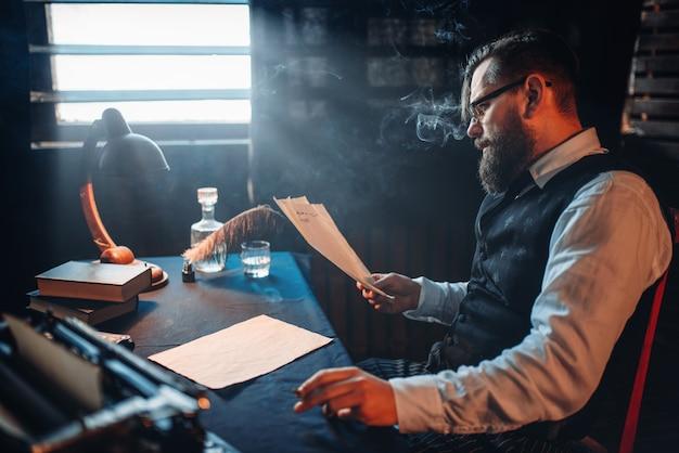 Écrivain barbu fume et lit un texte manuscrit