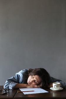 Écrivain femme endormie se trouve à l'intérieur