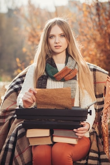 Écrivain femme travaille sur la vieille machine à écrire dans le parc en automne