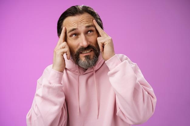 L'écrivain masculin mature perturbé intense et inquiet ne peut pas créer l'idée debout pressé toucher le front fronçant les sourcils regarder problème concentré non concentré, debout fond violet bouleversé distrait.