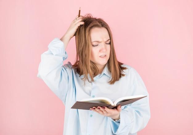 Une écrivaine en chemise bleue essaie de penser à quoi écrire dans un livre, se gratte la tête et tient un crayon et un livre dans ses mains sur un mur rose. journée internationale des écrivains