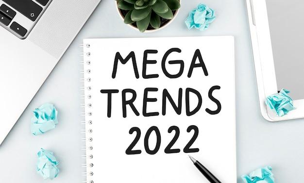 Écrivez mega trends 2022 sur le carnet. ordinateur portable, morceaux de papier, stylo et plante sur le bureau. mise à plat, vue de dessus. notion de planification.
