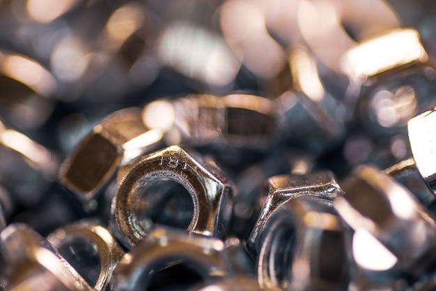 Écrous en métal chromé dans un contexte industriel d'ordre chaotique