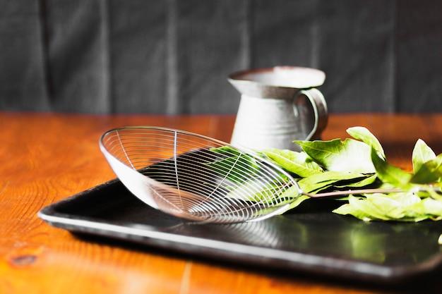Écumoire et cruche avec des feuilles dans un plateau noir sur la table