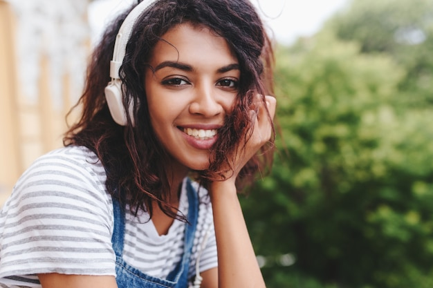 Ecxited girl porte une chemise rayée assise en plein air face avec main et écoute de la musique dans des écouteurs blancs