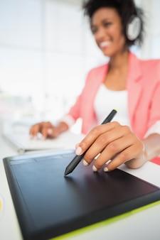Éditeur photo décontracté femme à l'aide de tablette graphique