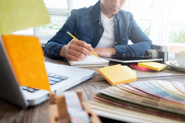 Éditeur de photo indépendant, artiste, graphiste travaillant au bureau dans un bureau créatif. dessin d'artiste sur une tablette graphique au bureau.