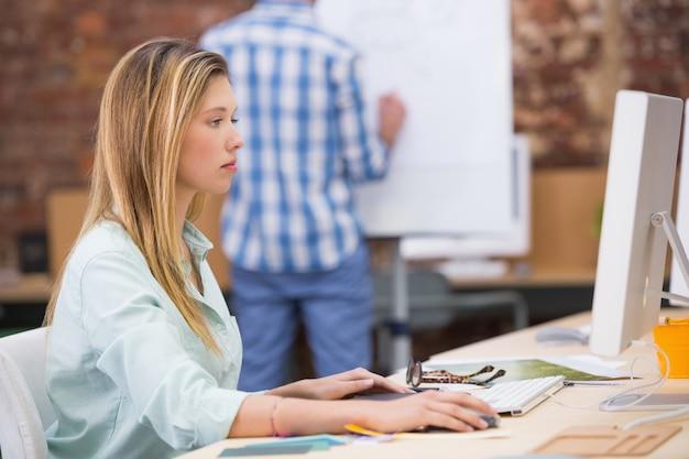 Éditeur de photos féminin concentré utilisant un ordinateur de bureau